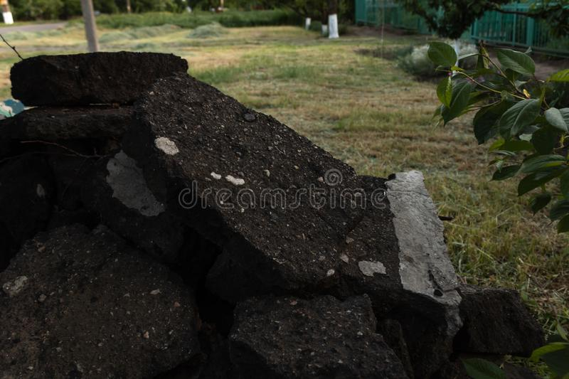 A pile of broken black asphalt lies in the garden near the house on mowed grass.  royalty free stock images