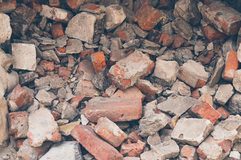 Pile of broken bricks, background. Texture, pattern, brick wall collapse. Destruction surface of building`s facade. Debris. stock photo