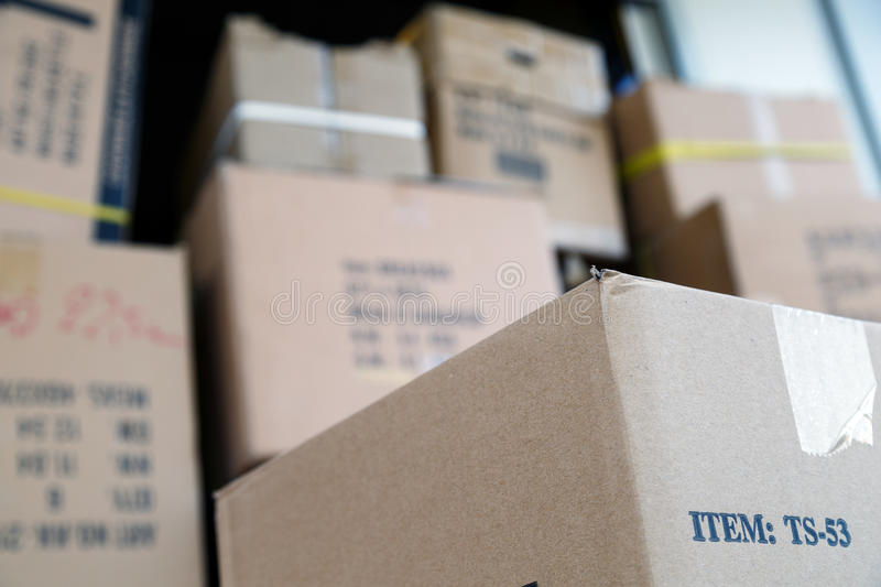 Pile of brown cardboard boxes at warehouse of market royalty free stock photo