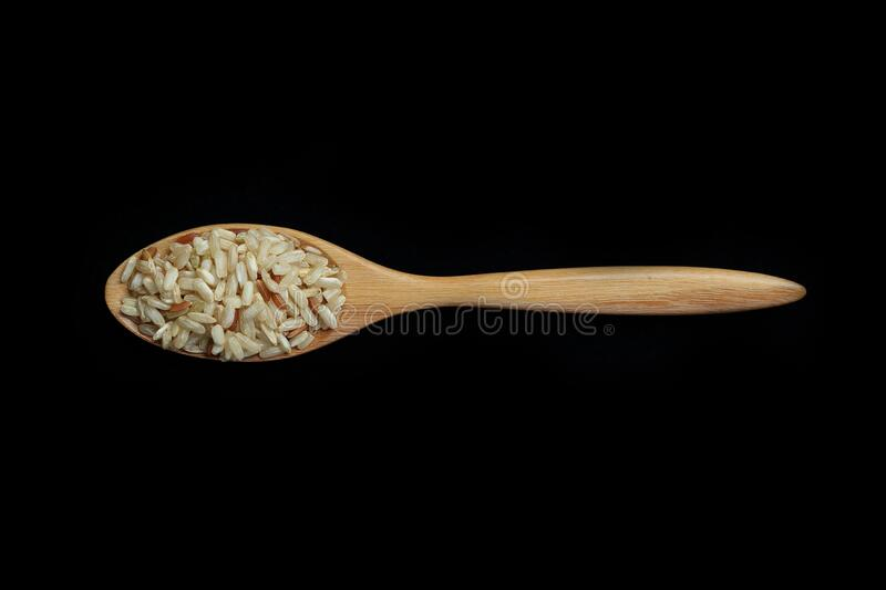 Pile of brown rice with spoon isolated on Black Background royalty free stock images