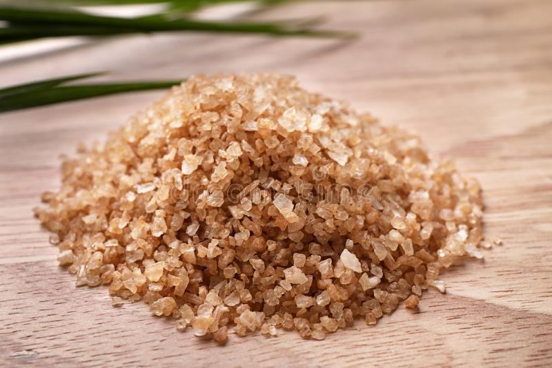 Pile of brown sea salt on wooden table. Spa treatment. Pile of brown sea salt on wooden table, closeup. Spa treatment royalty free stock images