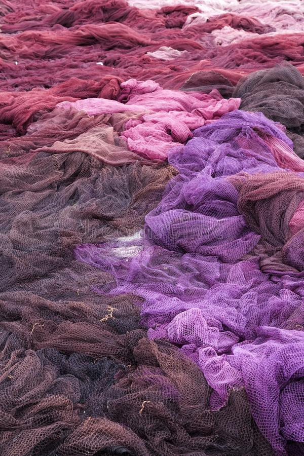 Pile of brown, violet and pink fishing nets royalty free stock photo