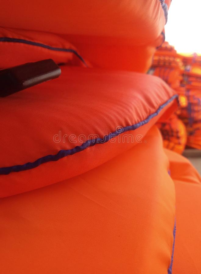 Pile of buoy. Orange life jacket outside the room. Arranged, clothes, delivery, forsale, lifejacket, lots, object, partially, red, stock, waistcoat, bright stock images