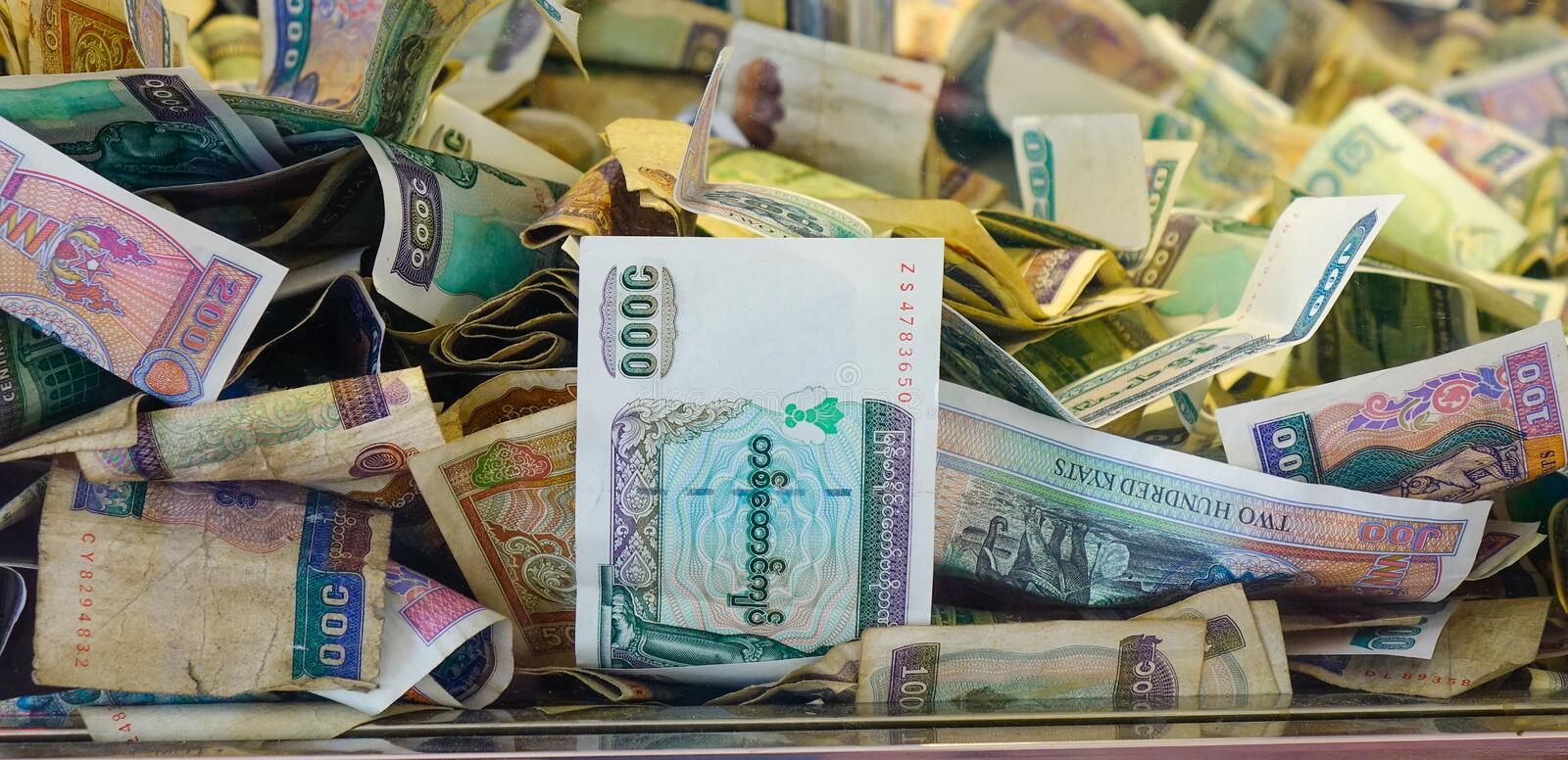 Pile of Burmese money in donation box stock images