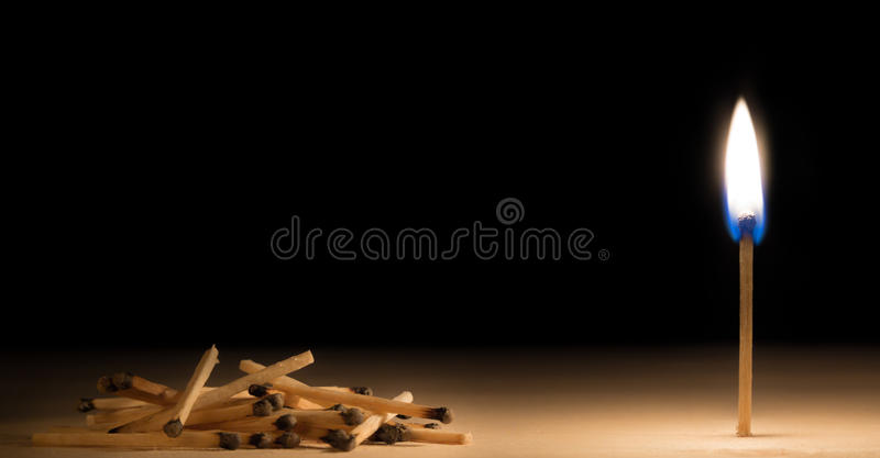 Pile of burnt matches laying down in front of one burnig match m. Etaphor on black background stock image