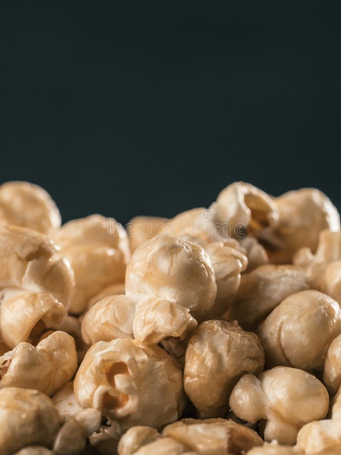 Pile of caramel corn on black background. Close up view of caramel corn on black background. Vertical. Copy space royalty free stock image