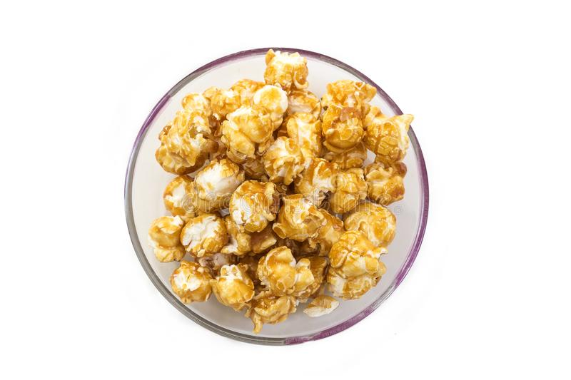 A pile of caramel corn in a bowl on a white background. A pile of caramel corn on white background stock photo