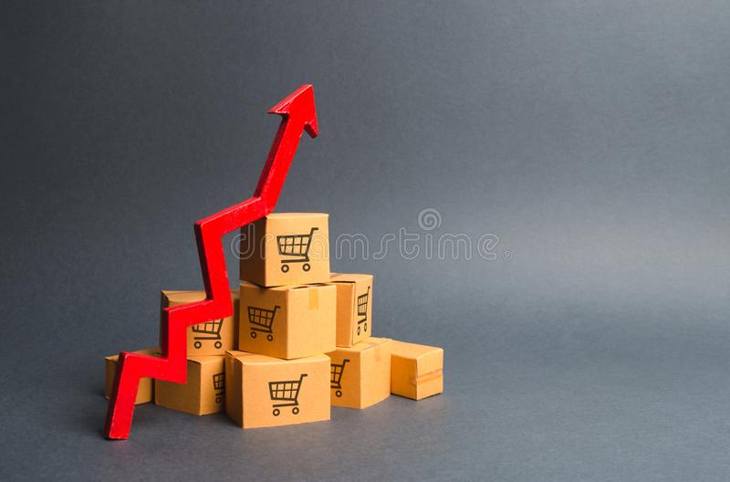 A pile of cardboard boxes with drawing of shopping carts and a red up arrow. The growth rate of production of goods and products royalty free stock images