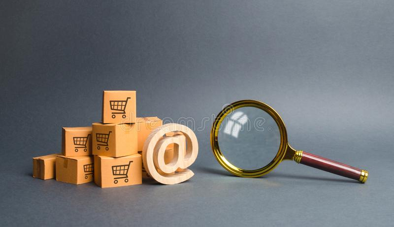 Pile of cardboard boxes with email symbol commercial AT and magnifying glass. online shopping and commerce. Search engine. And filtering. purchase through the royalty free stock photography