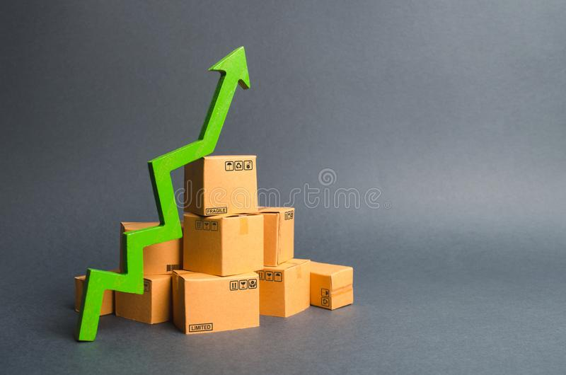 A pile of cardboard boxes and a green up arrow. The growth rate of production of goods and products, increasing economic. Indicators. Increasing consumer demand royalty free stock photo