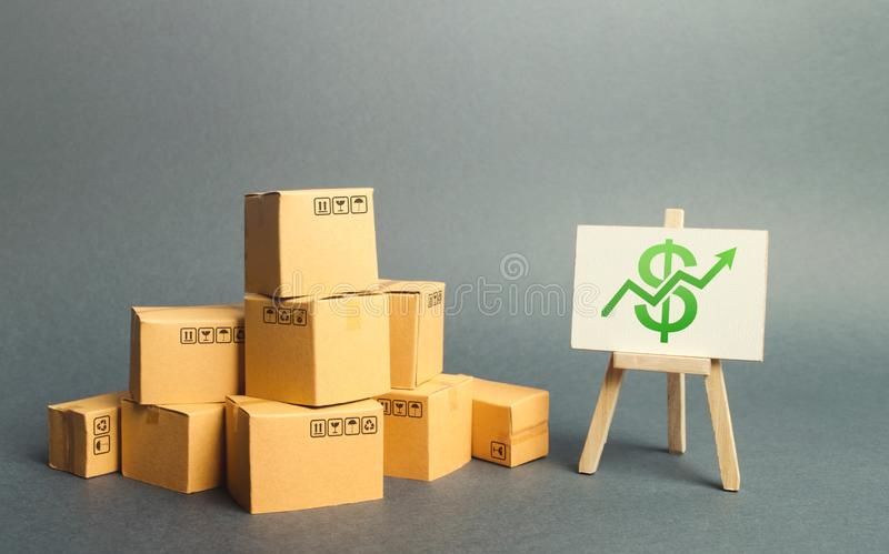 A pile of cardboard boxes and a stand with green arrow up. Increasing consumer demand. rate growth of production of goods. Increasing economic indicators stock photo