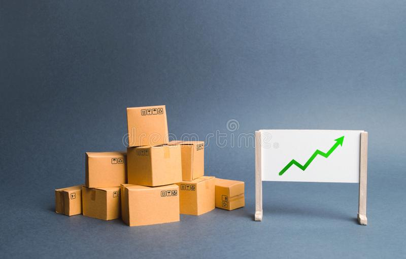 A pile of cardboard boxes and stand with green up arrow. Price increase. The growth rate of production. Increasing consumer demand. Exports and imports rise stock photography