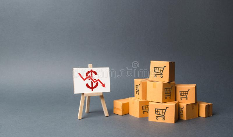 A pile of cardboard boxes and stand with a red down arrow. decline in the production of goods and products, the economic downturn royalty free stock photography