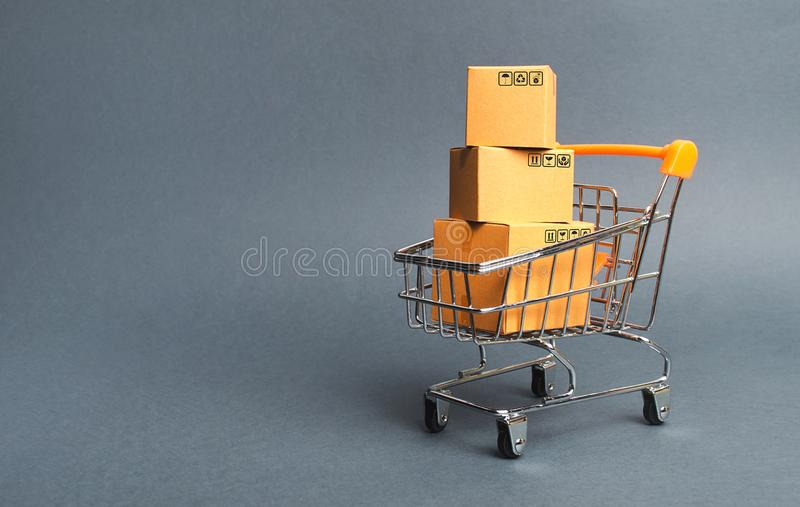 A pile of cardboard boxes in a supermarket trolley. concept of shopping in the online store . E-commerce, sales and sale of goods. Through online trading stock images