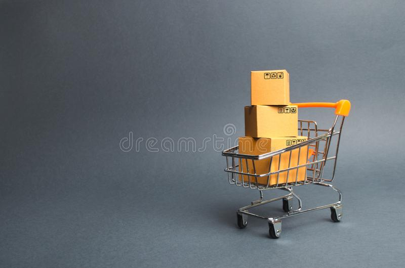 A pile of cardboard boxes in a supermarket trolley. concept of shopping in the online store . E-commerce, sales and sale of goods. Through online trading stock image