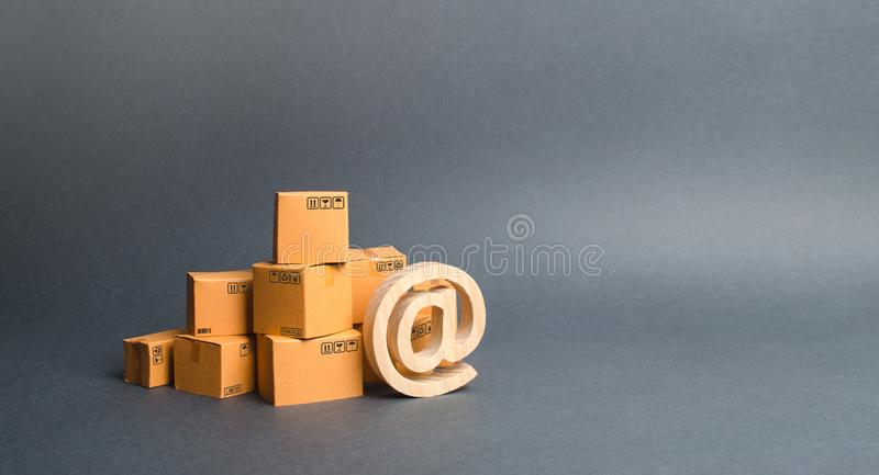 Pile of cardboard boxes and symbol commercial AT. shopping online. E-commerce. sales of goods and services through online trading. Platforms. development of royalty free stock photo
