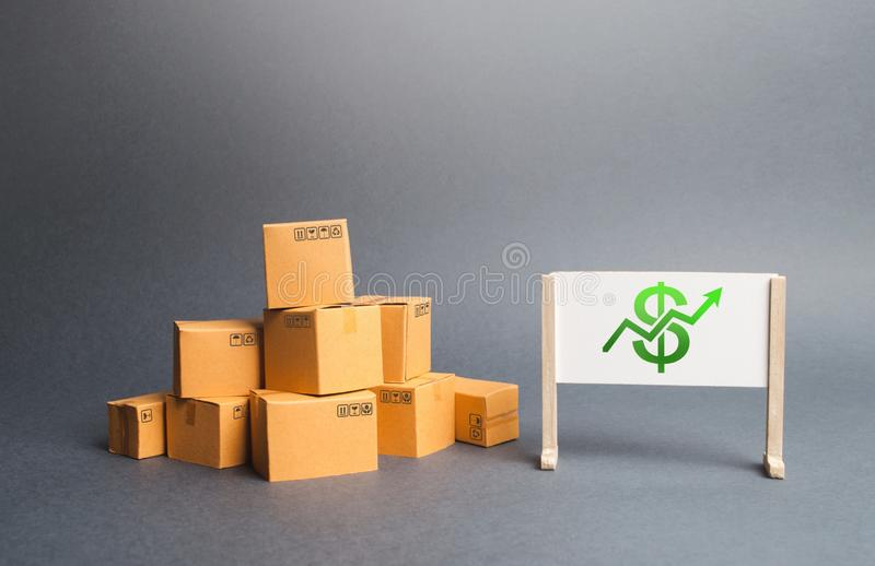 A pile of cardboard boxes and whiteboard with dollar sign and green up arrow. The growth rate of production. Increasing consumer. Demand. Growth of income from stock photo