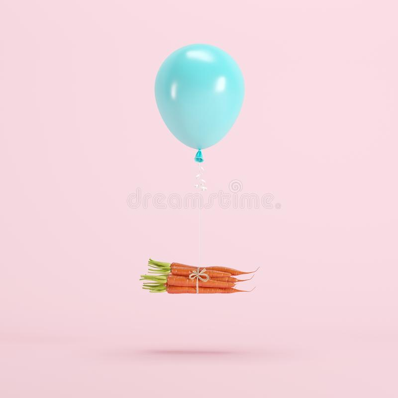 Pile of carrots attached with blue balloon floating on pastel pink background royalty free stock photography