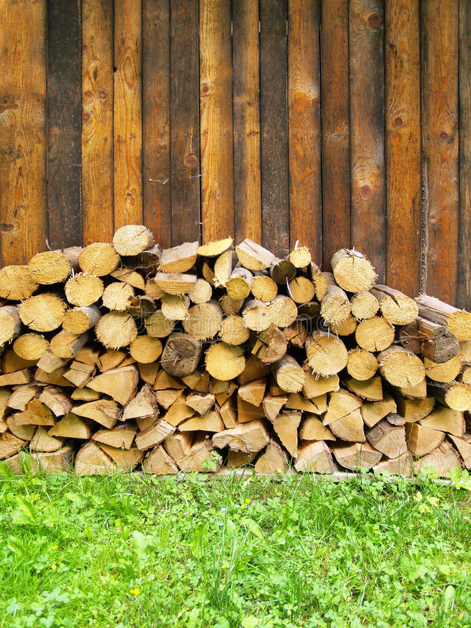 Pile of chopped logs. With wooden fence in background stock photos
