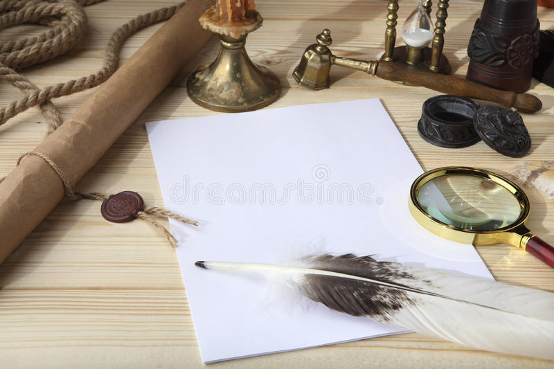 A pile of clean paper, a retro inkwell with black ink, a goose feather, magnifying glass, a scroll with a seal, an old hourglass a royalty free stock photo