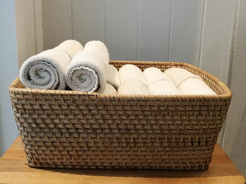 Pile of cloth, hand towel, table napkin, handkerchief on the basket in spa, bath room, toliet with blur white wooden wall backgrou stock image