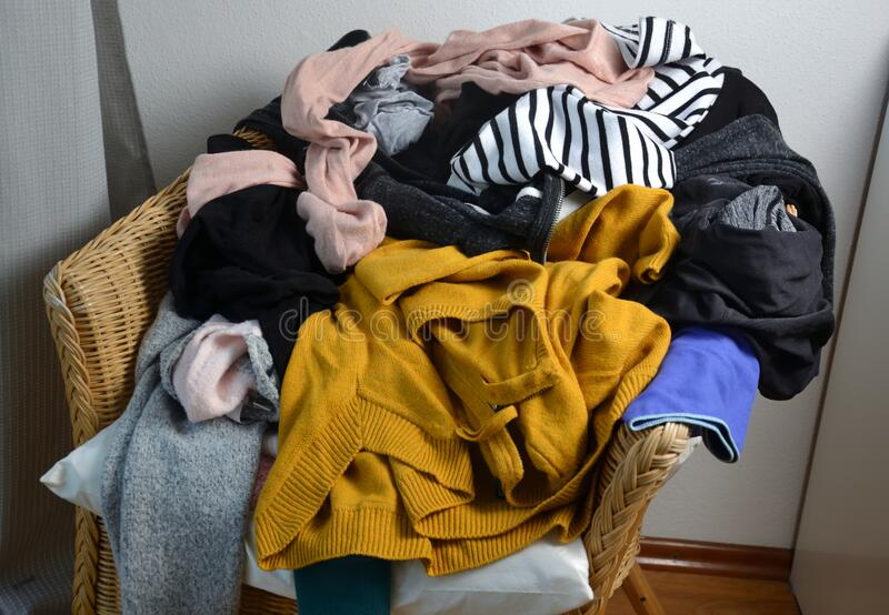 Pile of clothes on a chair. A pile of clothes on a chair stock photo