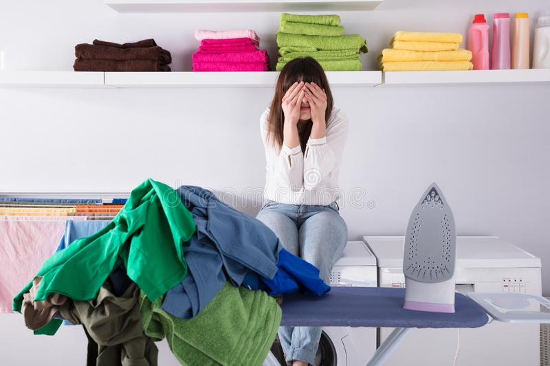 Pile Of Clothes And Iron On Ironing Board. Upset Woman Sitting Behind Pile Of Clothes And Iron On Ironing Board stock photos