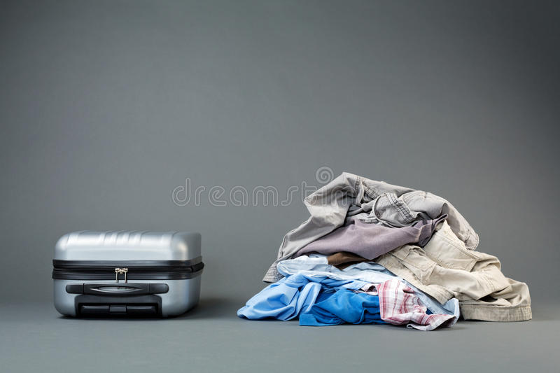 Pile of Clothes and a Suitcase. Trip preparation - a messy pile of clothes next to a lightweight suitcase royalty free stock image
