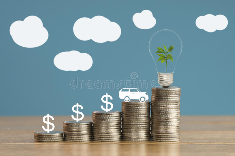 pile of coins and car with green small tree, light bulb, concept in save money, finance,loan royalty free stock photo