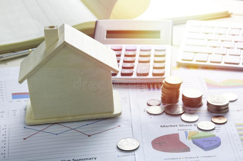 Pile of coins and home, concept in house finance on wood. Table royalty free stock image