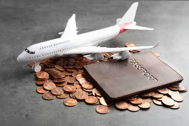 Pile of coins, passport and plane model. On grey background royalty free stock image