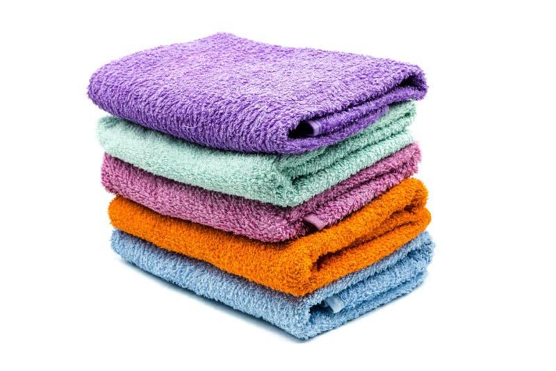 pile colorée de serviettes de bain d'isolement sur le fond blanc photos libres de droits
