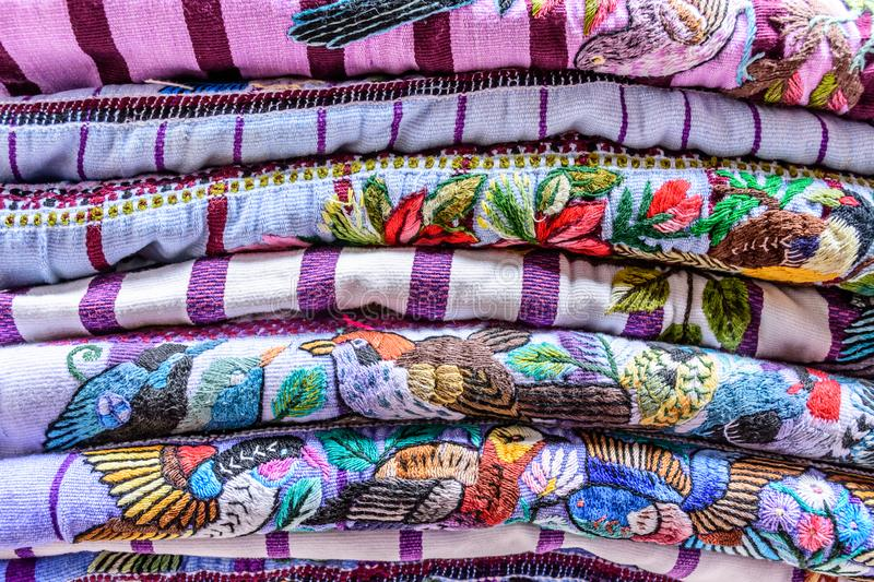 Pile of colorful handwoven Guatemalan blouses called huipiles. Pile of colorful handwoven Guatemalan indigenous blouses called huipiles made, worn & sold by royalty free stock photo