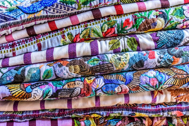 Pile of colorful handwoven Guatemalan blouses called huipiles. Pile of colorful handwoven Guatemalan indigenous blouses called huipiles made, worn & sold by royalty free stock image