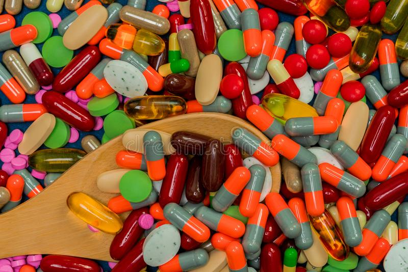 Pile of colorful pills and wood spoon. Medicine, vitamins, supplement and minerals. Antibiotics drug resistance and drug use royalty free stock photo
