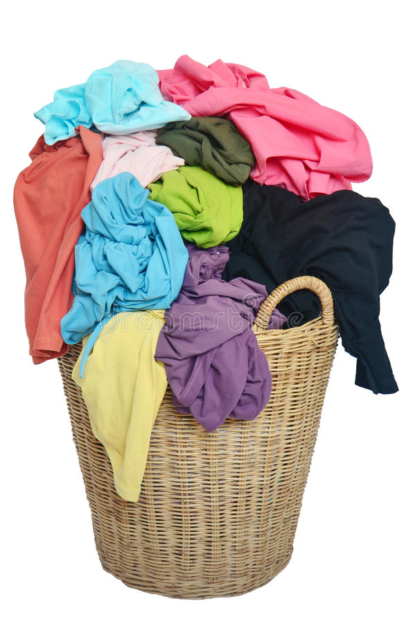 pile of colorful shirts in a wicker basket, isolated white background stock photo