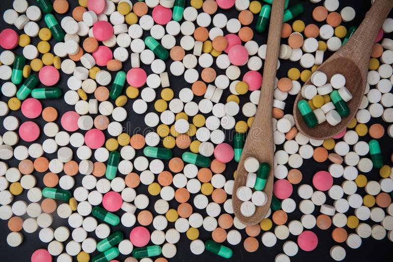 Pile of colorful tablets and capsules pills and wood spoon on bl stock photography