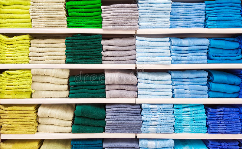 Pile of colorful towels at shelf stock photos