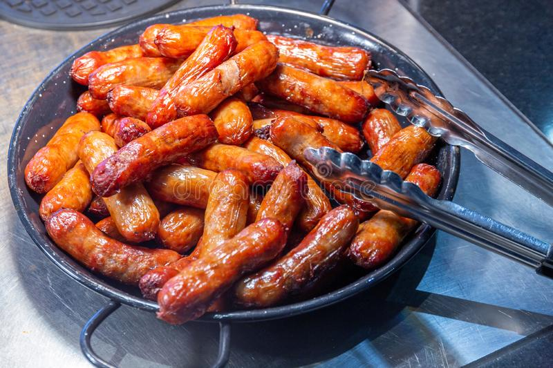 Pile of cooked sausages in a skillet pan stock photo