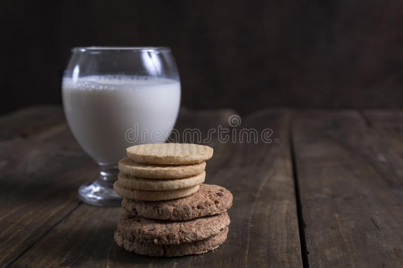 Pile of cookies and milk on wooden table royalty free stock photos