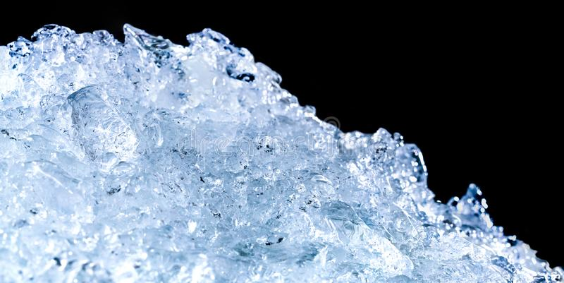 Pile of crushed ice cubes on dark background with copy space. Crushed ice cubes foreground for beverages royalty free stock images
