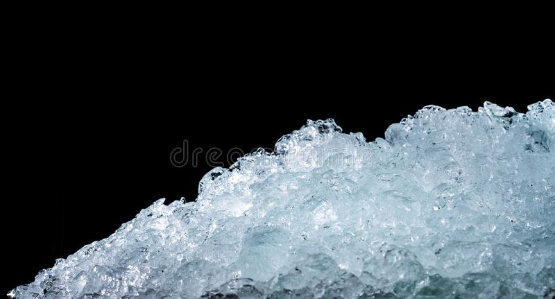 Pile of crushed ice cubes on dark background with copy space. Crushed ice cubes foreground for beverages, beer, whisky, fruit stock photos