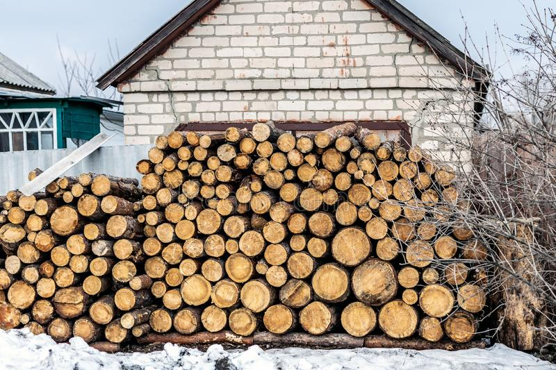 Pile of cutted wooden log stacked near house. Firewood timber material stack prepared for heating in winter at old rural building royalty free stock photography