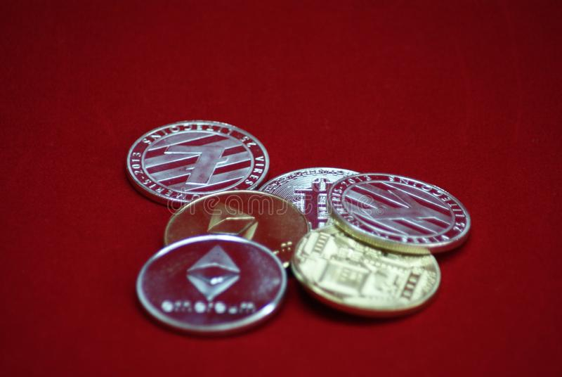 Pile d'or et de pièces de monnaie argentées de cryptocurrency sur un fond rouge de velours photographie stock