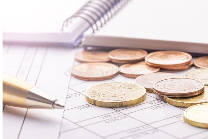 Pile d'euro euro pièces de monnaie sur la vieille table en bois noire Stylo, carnet et documents comptables avec des nombres photos stock