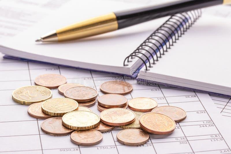Pile d'euro euro pièces de monnaie sur la vieille table en bois noire Stylo, carnet et documents comptables avec des nombres photos libres de droits