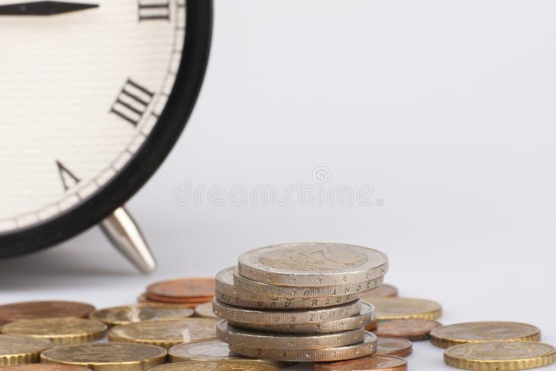 Pile d'euro pi?ces de monnaie d'isolement sur le fond blanc Concept global, de temps et d'affaires Horloge ronde de cru sur la pi image libre de droits
