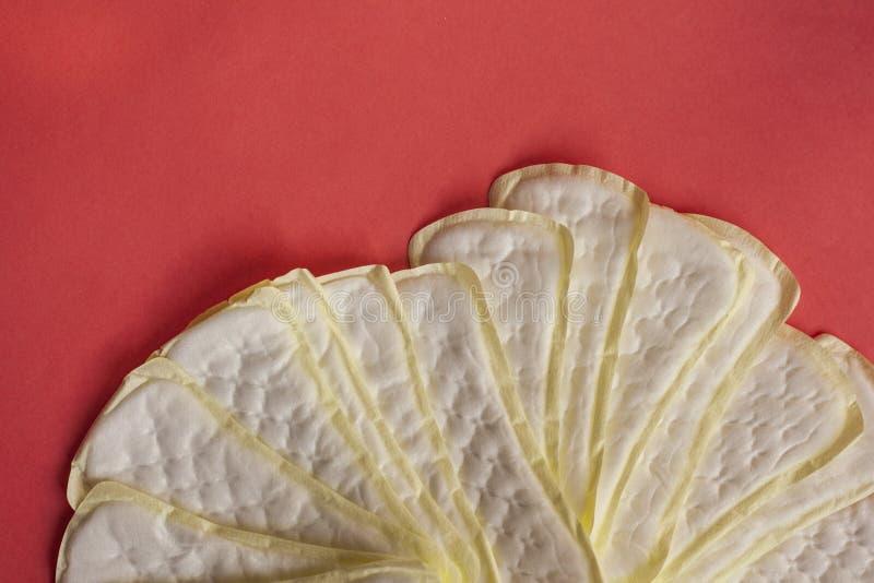 Pile d'hygi?ne f?minine ou de protections menstruelles sur le fond rouge Serviettes hygi?niques pour des femmes images libres de droits