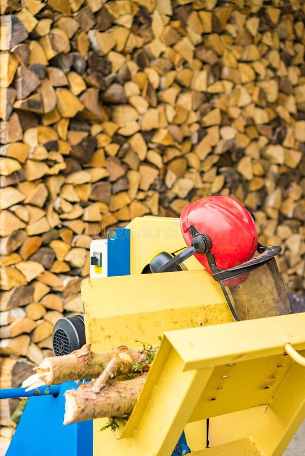 Pile de bois de chauffage avec la scie circulaire et le casque rouge images stock