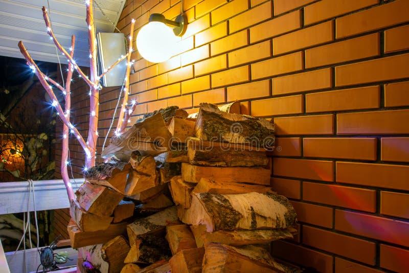Pile de bois de chauffage de bouleau pour la cheminée Le mur de briques et la lanterne rouges brûle sur le fond Nuit de l'hiver photos libres de droits